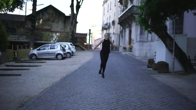 vídeos de stock e filmes b-roll de blonde woman skipping along a street - people lisbon