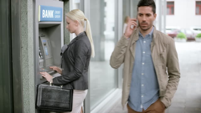 blonde woman stepping to the atm machine and making a withdrawal - banks and atms stock videos & royalty-free footage