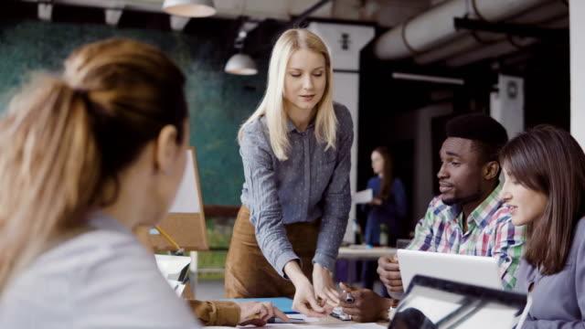 Líder de equipe de mulher loira dando direção à equipe de raça mista de jovens. Reunião de negócios criativos no escritório moderno - vídeo