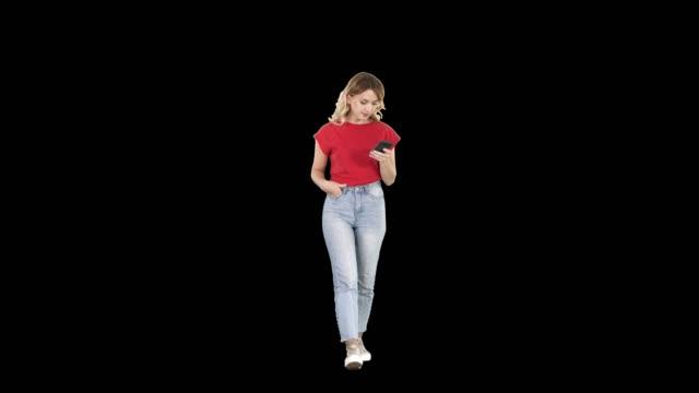 vídeos de stock, filmes e b-roll de mensagens de mulher loira com seu telefone inteligente andando, alpha channel - estreito mar