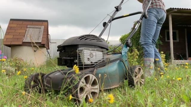 blonde frau versucht, motor eines rasenmähers zu starten, sommerarbeit im garten, schneiden grün gras - gärtnerisch gestaltet stock-videos und b-roll-filmmaterial