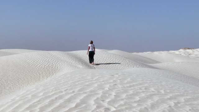 Blonde woman walking in the desert