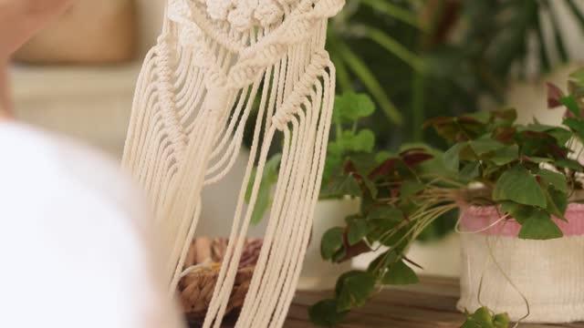 vídeos de stock, filmes e b-roll de uma mulher loira tecendo macramê de fios leves em uma oficina em casa. conceito artesanal. - boho