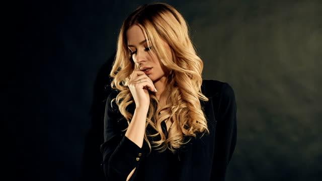 ポーズ スタジオで黒の背景に黒い服で巻き毛のブロンドの女性 - 都会的ファッション点の映像素材/bロール