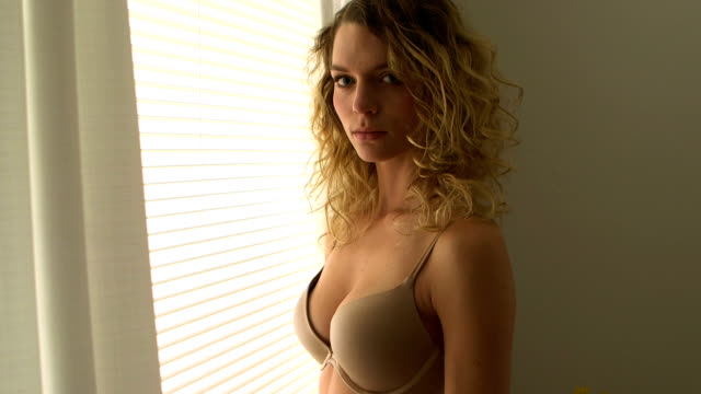 Blonde woman with curly hair standing by window in lingerie video