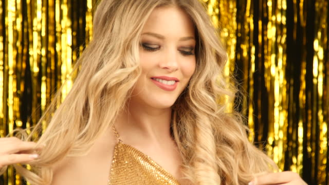 blonde woman with gold shirt smiling with gold shiny background moving her hair video