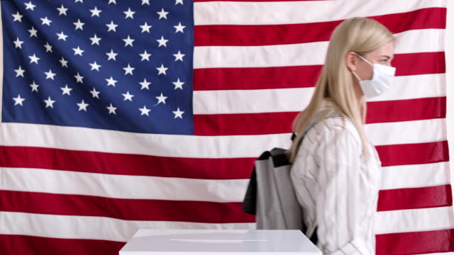 vidéos et rushes de femme caucasienne aux cheveux blonds mettant le bulletin dans l'urne - démocratie
