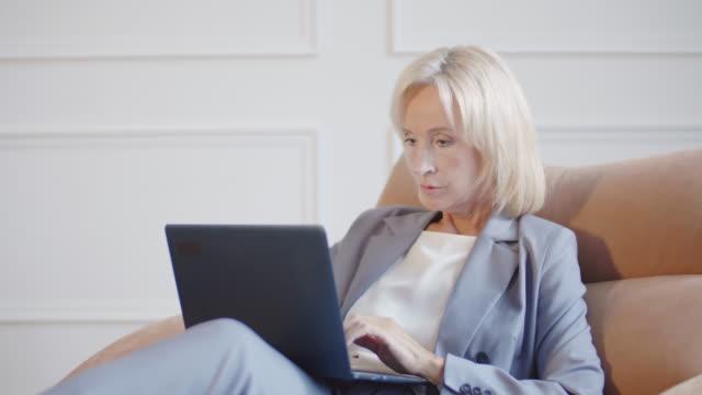 stockvideo's en b-roll-footage met blond-haired vrouwelijke advocaat die aan laptop werkt - four lawyers