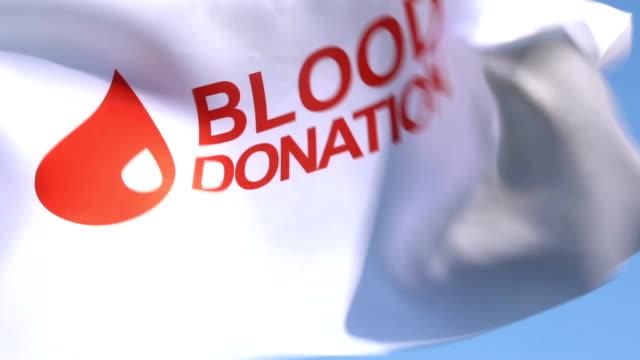 vídeos de stock e filmes b-roll de blood donation flag waving in sky - blood donation