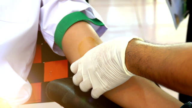 Blood donation.  The doctor and nurse put the needle into the arm of the donor. In order to go to the patient and some parts to test the disease in the laboratory. video