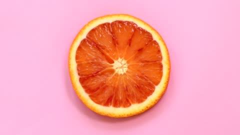 vídeos y material grabado en eventos de stock de rebanada de naranja sangre rotación de la vista superior sobre fondo rosado - rebanada