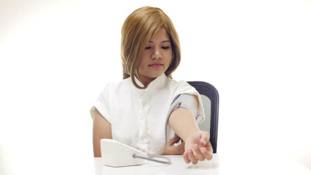 blood pressure check woman checking blood pressure with digital blood pressure gauge sleeve stock videos & royalty-free footage
