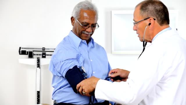 Blood Pressure Measurement HD1080p, 29.97fps.  Patient getting his blood pressure taken in a doctor's office. blood pressure gauge stock videos & royalty-free footage