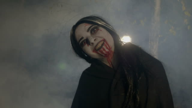Bloody evil female vampire enjoying the foggy halloween night in the woods and laughing video