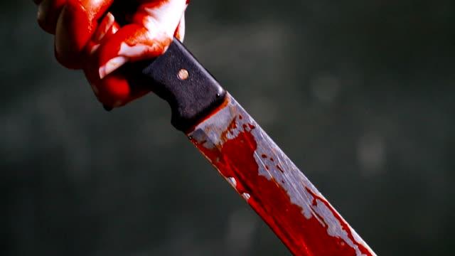 vidéos et rushes de couteau sanglant. main tient un couteau maculé de sang - sang