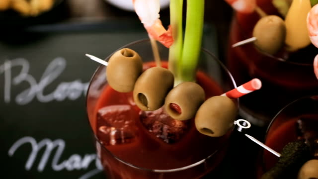 Bloody mary cocktail garnished with olives, pickles, and cocktail shrimp. Bloody mary cocktail garnished with olives, pickles, and cocktail shrimp. garnish stock videos & royalty-free footage