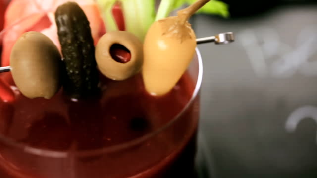 Bloody mary cocktail garnished with olives, pickles, and cocktail shrimp. video