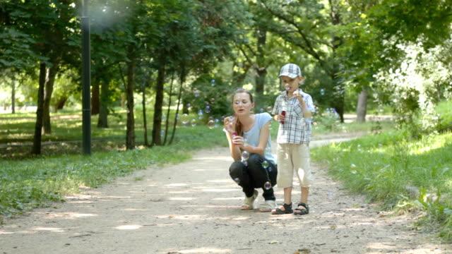 Soplando burbujas con un niño en el parque - vídeo