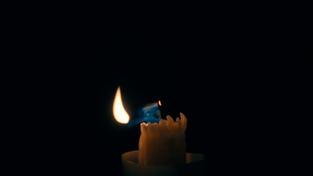 Blowing burning candles on a black background.  Slow mo, slo mo video