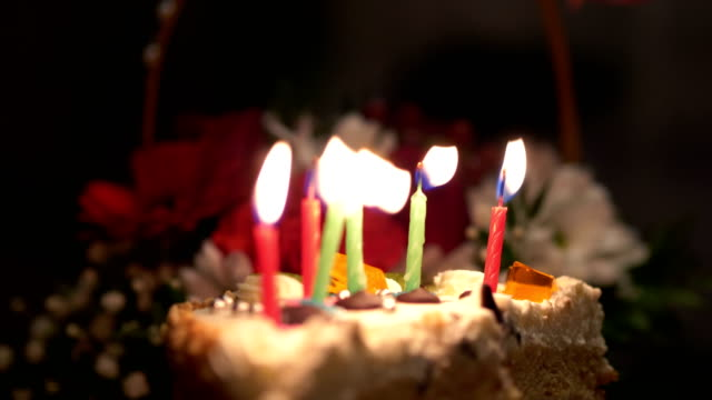 4kスローモーション60fpsでバースデーケーキに燃えるキャンドルを吹く - 親族会点の映像素材/bロール
