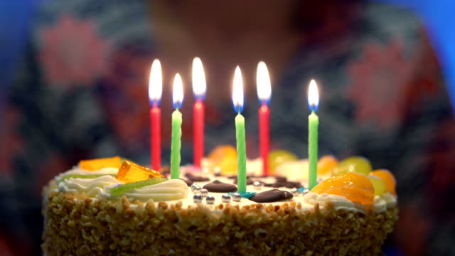 Blowing candles on the birthday cake in 4k slow motion 60fps Blowing candles on the birthday cake in 4k slow motion 60fps birthday background stock videos & royalty-free footage