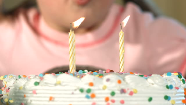 Blowing out candles, closeup, slow motion video