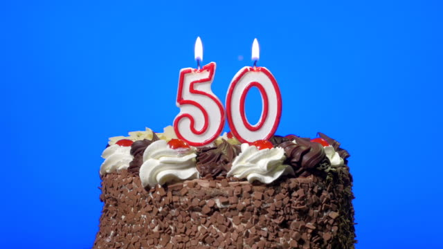 Blowing out number fifty birthday candles on a delicious chocolate cake, blue screen video