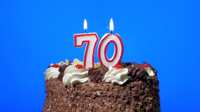 Blowing out number seventy birthday candles on a delicious chocolate cake, blue screen video
