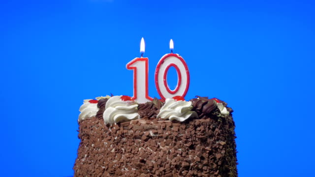 Blowing out number ten birthday candles on a delicious chocolate cake, blue screen video