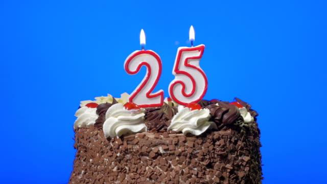 blasen sie number twenty-five geburtstag kerzen auf einem köstlichen schokoladenkuchen, blau bildschirm - zahl 25 stock-videos und b-roll-filmmaterial