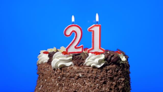 vidéos et rushes de soufflant le vingt-et-un anniversaire bougies sur un délicieux gâteau au chocolat, bleu écran - 20 24 ans