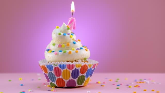 blåser ut ljusen på födelsedag dekorerade cupcake med strössel - glidande skott - confetti bildbanksvideor och videomaterial från bakom kulisserna