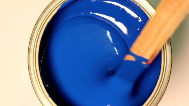 vidéos et rushes de mélange de peinture acrylique bleu avec mélangeur à main - bois texture