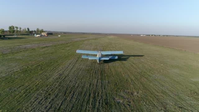vidéos et rushes de avion bleue prend son envol sur le champ contre le ciel et l'horizon en ligne au printemps - herbicide