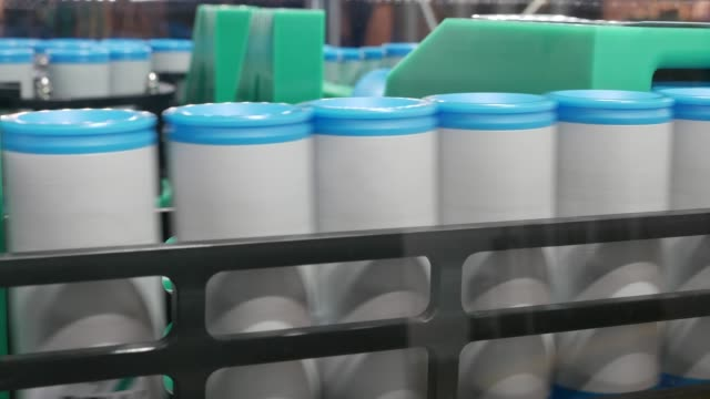 Blue and white plastic cans on an industrial conveyor belt in a factory – 4K video