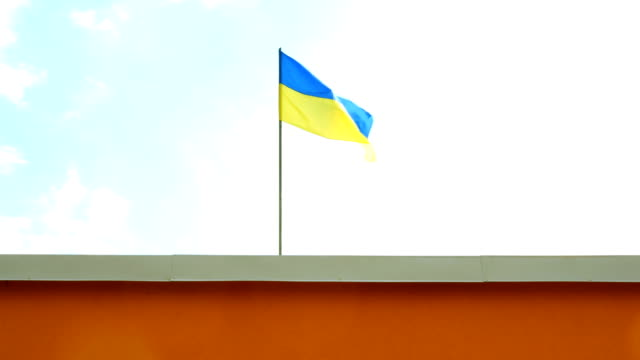Blue and yellow Ukrainian flag on a flagpole is installed above the roof of the house. Blue and yellow Ukrainian flag on a flagpole is installed above the roof of the house and fluttering in the wind. Against the blue sky. allegory painting stock videos & royalty-free footage
