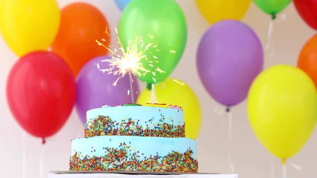 Blue Birthday cake with sparkler and colorful balloons video