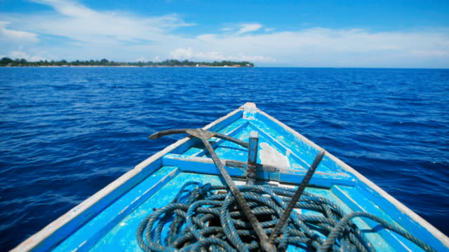 Blue boat with an anchor and a long rope on board, swaying from the wind, directed rapidly tem on the blue ocean to the island video