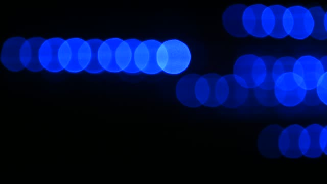 Blue bokeh circles move over black background Blue light bokeh circles move horizontally over black background dark blue stock videos & royalty-free footage