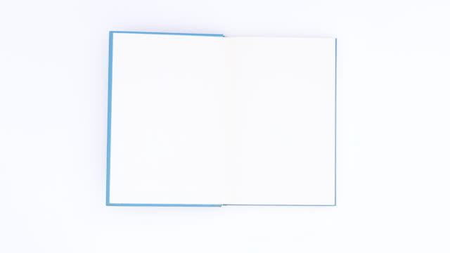 青い本が白いテーマで開いて現れます。モーションを停止する - 本点の映像素材/bロール