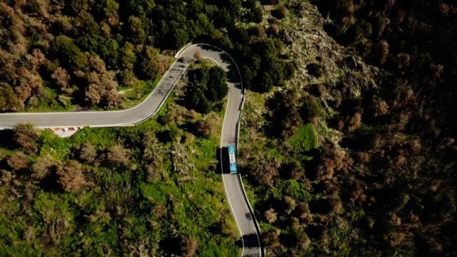 Ônibus azul vira à esquerda em uma vista aérea de estrada de montanha. Calçada perigosa floresta estreitas. Segurança do tráfego rodoviário. Viagens 4K - vídeo