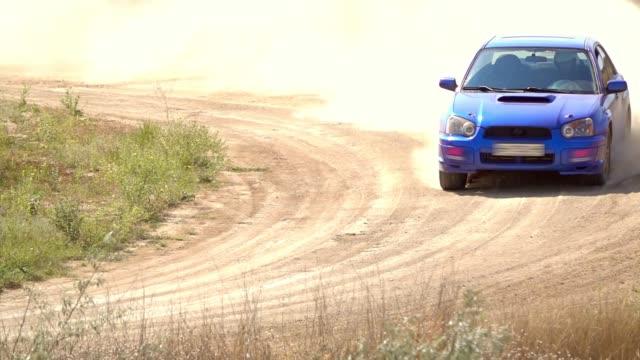 stockvideo's en b-roll-footage met blauwe auto rijdt een extreme bocht. slow motion - kampioenschap