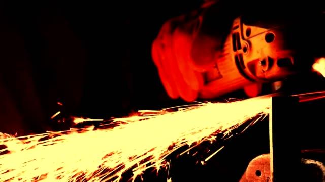 Blue collar mechanic using grinder in workshop video