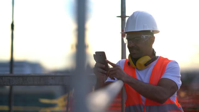 vídeos y material grabado en eventos de stock de trabajador de cuello azul en una construcción tomando un descanso apoyado en un andamio mientras charla sobre su smartphone sonriendo - obrero de la construcción