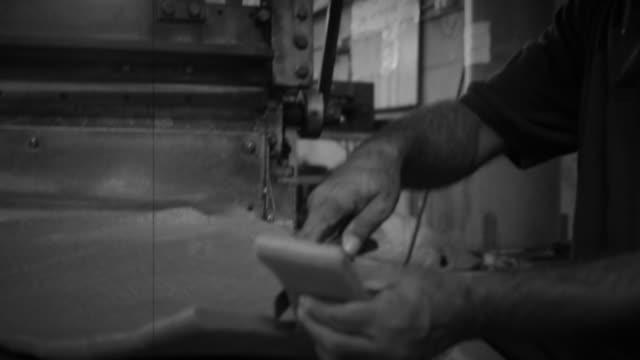 Blue Collar Worker Cutting Raw Material near a Machinery