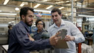 istock Blue collar worker talking to male supervisor while showing him a spare part at the production line 1206324628