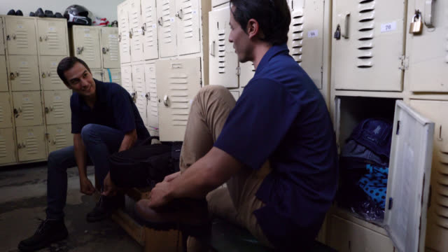 Blue collar workers getting changed for their work shift at the factory talking Blue collar workers getting changed for their work shift at the factory talking and smiling locker stock videos & royalty-free footage
