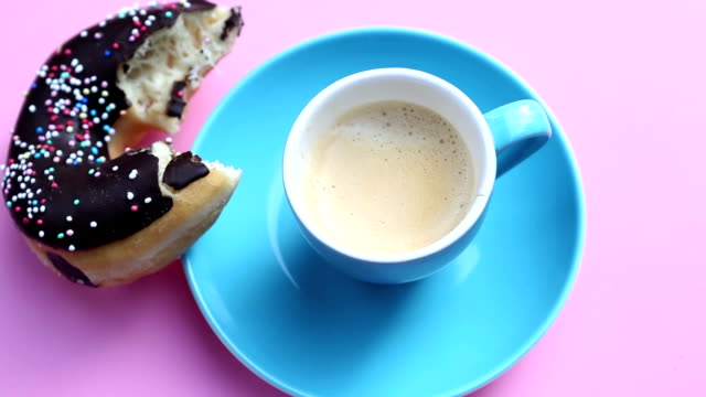 blue cup of coffee with half bitten donut on rotating pink plate