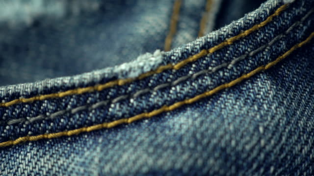 blue denim jeans close up 4k stock footage with a sliding camera move. - jeans video stock e b–roll