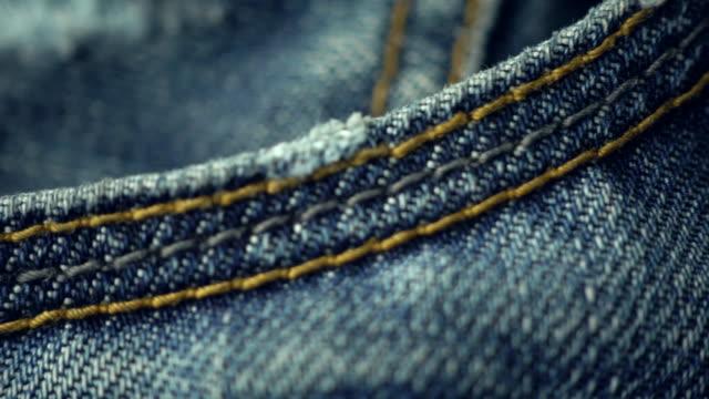 blue denim jeans close up 4k stock footage with a sliding camera move. - dżinsy filmów i materiałów b-roll